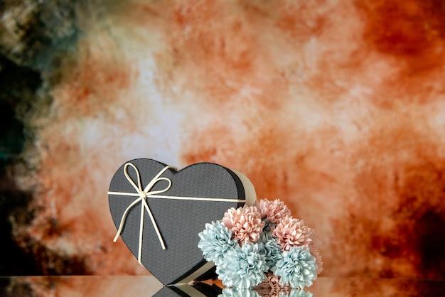 Vista frontale della confezione regalo a cuore con fiori colorati con copertina nera su sfondo astratto beige nero con copia posto