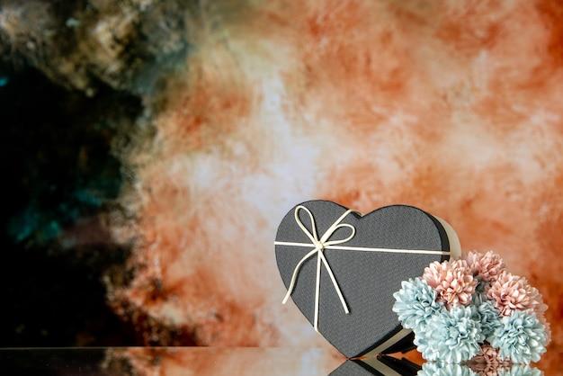 Vista frontale della confezione regalo a cuore con fiori colorati con copertina nera su sfondo astratto beige nero