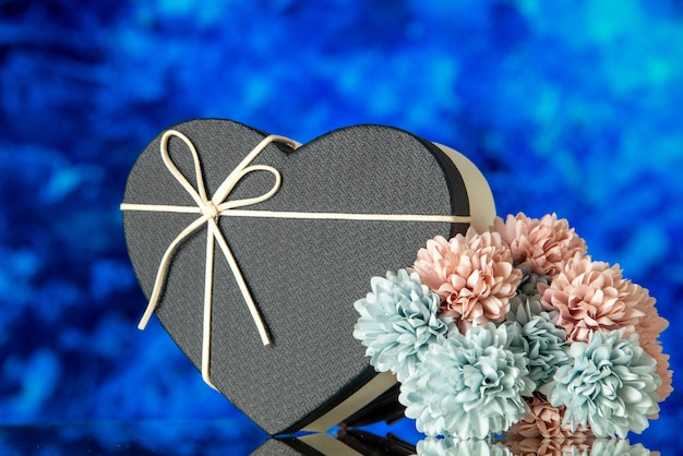 Front view of heart giftbox with black cover and colored flowers on blue abstract background