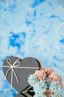Front view of heart giftbox with black cover colored flowers on ice blue blurred background with copy place