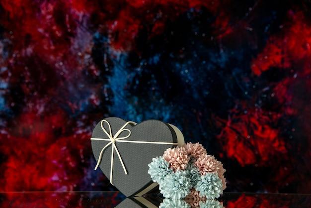 Fiori colorati scatola a forma di cuore vista frontale su sfondo astratto rosso scuro spazio libero