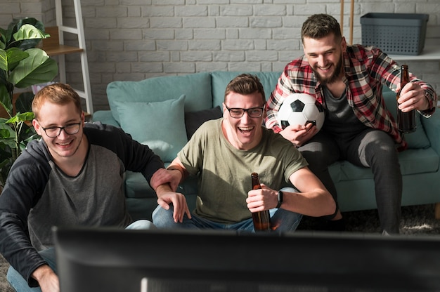 Front view of heerful male friends watching sports on tv with football