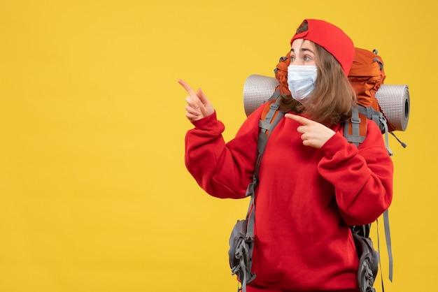 左のバックパックとマスクポインティング指を持つ正面図のヒッチハイカーの女の子