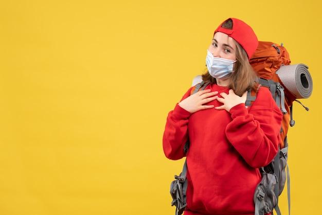 彼女の胸に手を置くバックパックとマスクを持つ正面図のヒッチハイカーの女の子