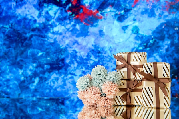 I fiori dei regali di festa di vista frontale si riflettono sullo specchio su fondo blu
