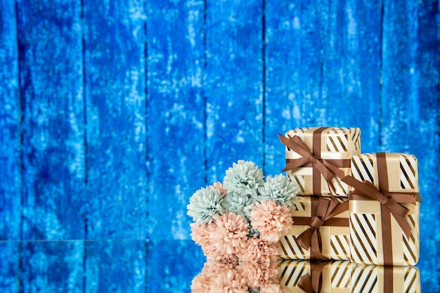 I fiori dei regali di festa di vista frontale si riflettono sullo specchio su fondo di legno blu