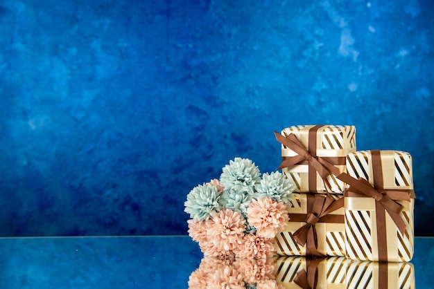 I fiori dei regali di festa di vista frontale si riflettono sullo specchio su sfondo blu scuro