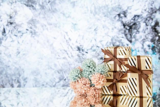 I fiori dei regali di festa di vista frontale si riflettono sullo specchio su fondo astratto grigio