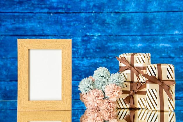 I fiori della cornice della foto dei regali di festa di vista frontale si riflettono sullo specchio su fondo di legno blu