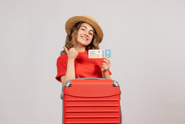Front view of holiday girl with her valise holding ticket giving thumbs up