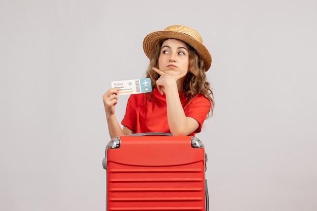 Vista frontale della ragazza di vacanza con la sua valigia che tiene il biglietto mettendo la mano sul mento