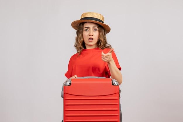 Vista frontale della ragazza di vacanza con la sua valigia che punta davanti in piedi sul muro bianco