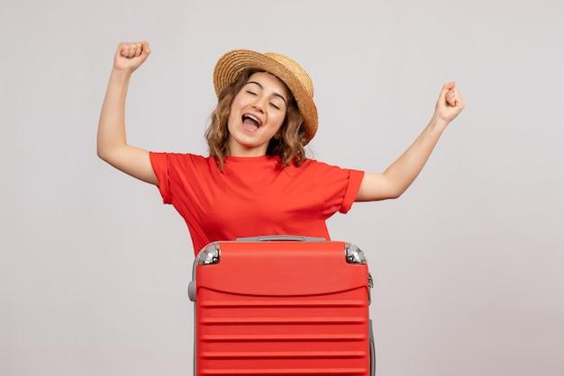 Vista frontale della ragazza di vacanza con la sua valigia in piedi sul muro bianco