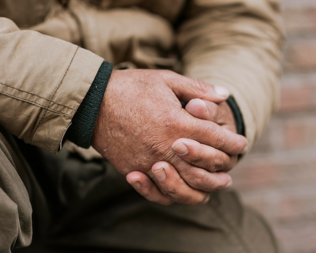 Vista frontale delle mani dell'uomo senza casa