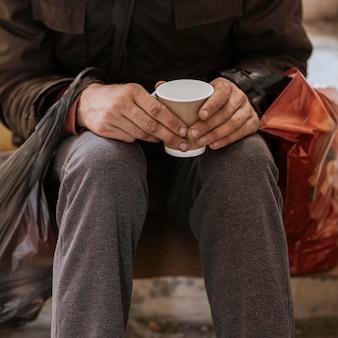 Vista frontale del senzatetto che tiene tazza e sacchetto di plastica