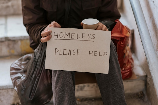 Front view of homeless man holding help sign and plastic bag