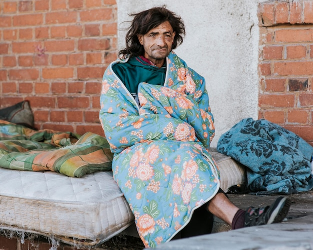 Front view of homeless man on mattress outdoors under blanket