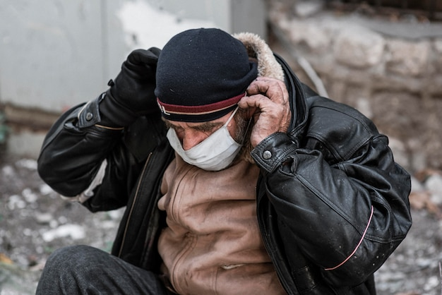 Front view of homeless man outdoors putting on medical mask