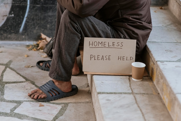Front view of homeless man on stairs with help sign and cup