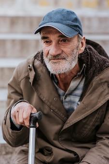 Vista frontale di un senzatetto con barba e bastone
