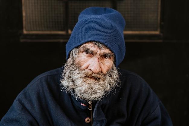 Vista frontale di un senzatetto con la barba