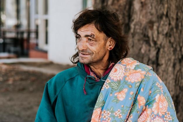 Vista frontale di un senzatetto con coperta sulla spalla