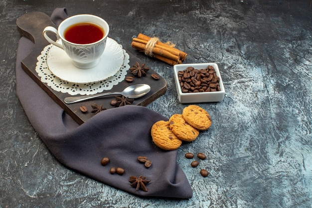 Front view of homemade cookies cinnamon limes and a cup of tea on wooden cutting board coffee beans on ice background