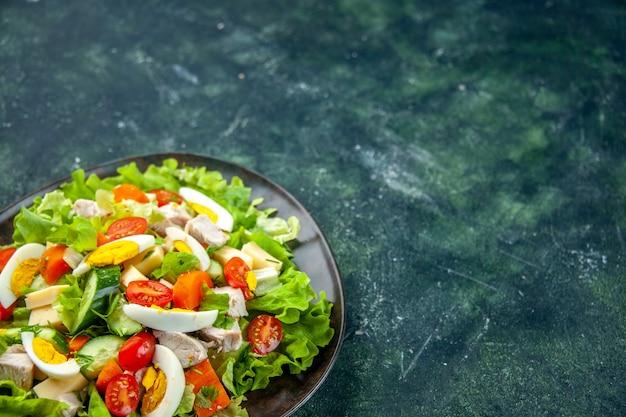 Vista frontale di deliziosa insalata fatta in casa con molti ingredienti in un piatto sul lato destro su sfondo di colori mix verde nero con spazio libero