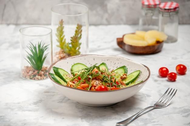 Vista frontale di sana e deliziosa insalata vegana fatta in casa decorata con cetrioli tritati in una ciotola forchetta ananas pomodori secchi su superficie bianca macchiata con spazio libero