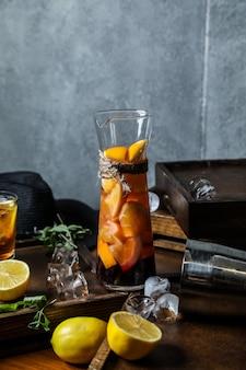 Домашний холодный чай с лимоном в графине, вид спереди