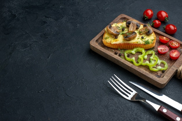 Front view of homemade tasty snack with mushrooms and chopped vegetables on wooden board cutlery set on black background