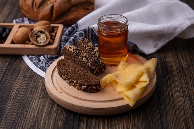 木製の背景にクルミとスタンドに黒いパンとチーズと瓶の中の正面の蜂蜜