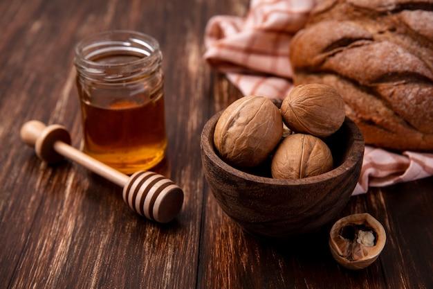 木製の背景にクルミと黒パンのパンと瓶の中の正面の蜂蜜