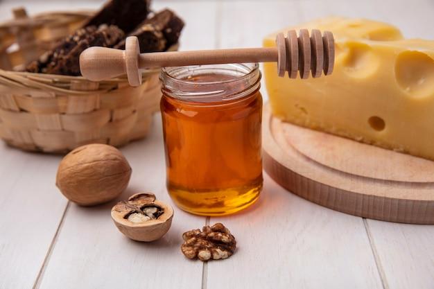 Miele di vista frontale in un barattolo con noci di formaggio e pane nero su sfondo bianco