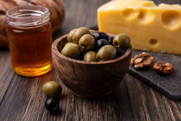 Front view honey in a jar with maasdam cheese on a stand and olives on the table