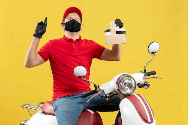 Vista frontale dell'uomo speranzoso del corriere che indossa guanti rossi del cappello e della camicetta nella mascherina medica che si siede sullo scooter che mostra gli ordini