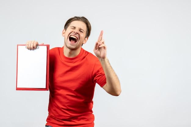 Vista frontale del giovane emotivo speranzoso in camicetta rossa che tiene documento su priorità bassa bianca