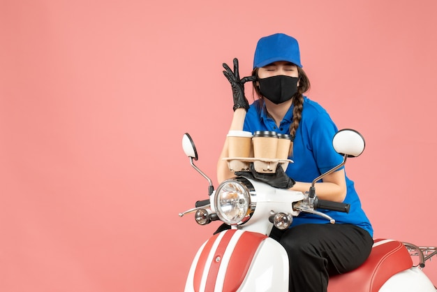 Front view of hopeful female delivery person wearing medical mask and gloves sitting on scooter holding orders on pastel peach background