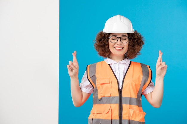 Front view hoping female builder in uniform on blue