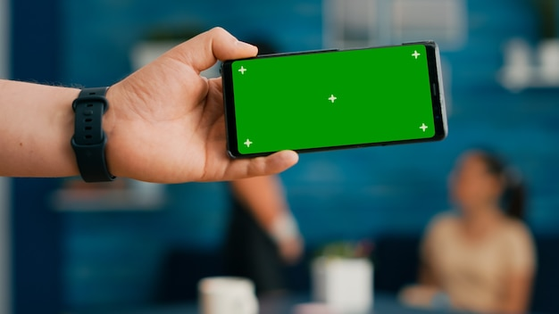Front view of horizontal isolated mock up green screen chroma key display of modern phone. two collegues talking about internet browsing and social media in home studio background