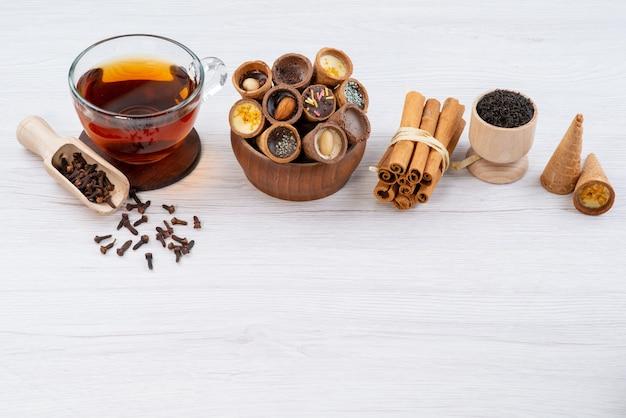 Una vista frontale di corna e cannella insieme a una tazza di tè su bianco, caramella di colore della bevanda del dessert