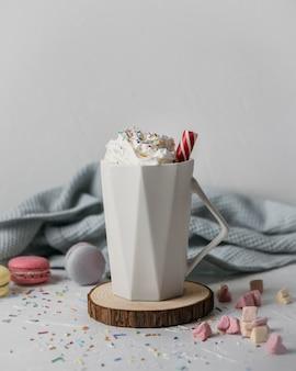 Горячий шоколад со взбитыми сливками в кружке, вид спереди