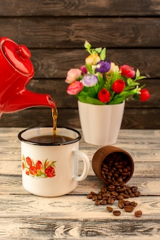 Front view of hot tea pouring from red kettle with brown coffee seeds and flowers on the wooden desk