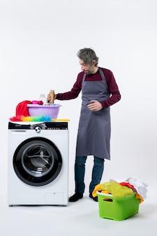 Governante di vista frontale in grembiule che tiene detersivo in piedi vicino a una lavatrice su sfondo bianco
