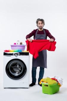 白い背景の上の洗濯機の近くに立っているtシャツを保持しているエプロンの正面図の家政婦