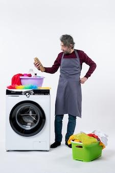 白い背景の上の洗濯機の近くに立っている洗剤を見ているエプロンの正面図の家政婦