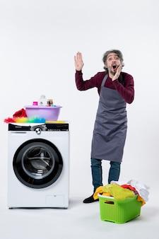 Uomo della governante vista frontale che chiama qualcuno in piedi vicino al cesto della biancheria della lavatrice su sfondo bianco