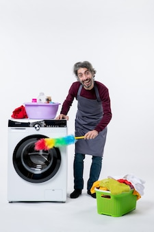 흰색 배경에 먼지떨이 세탁 바구니가 있는 세탁기를 청소하는 전면 보기 가정부 남자