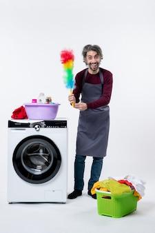 Uomo della governante vista frontale che tiene uno spolverino in piedi vicino alla lavatrice su sfondo bianco
