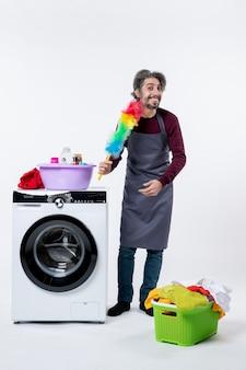 Uomo della governante vista frontale che tiene uno spolverino di piume in piedi vicino alla lavatrice su sfondo bianco isolato